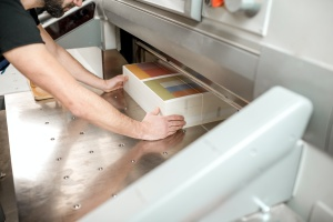 man lining up a stack of paper for cutting at a Bulk Commercial Printing