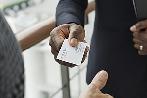 a business owner giving out his business card to a customer