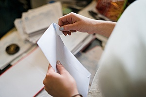 an individual opening a custom envelope to read a letter