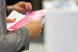 individuals reading business flyers they received for an event