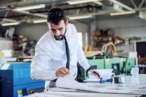 ardworking caucasian bearded controller looking at printed sheets in commercial printing company