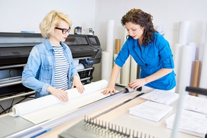 two modern young women working in printing shop looking at commercial printing company