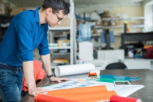 male designer in blue shirt standing at table and analyzing quality of banner